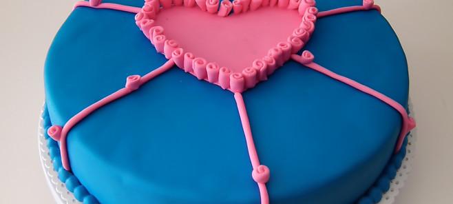 Torta pasta di zucchero Cuore, con base di pan di spagna farcito con crema al cioccolato fondente, decorato con un cuore di dolci roselline in pasta di zucchero.