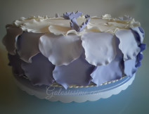 Torta pasta di zucchero Petali, a base di pan di Spagna e farcita di crema pasticcera con fragole.