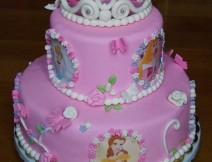 torta pasta di zucchero principesse Disney, pan di spagna alla vaniglia farcito con crema pasticcera e gocce di cioccolata, coperta e decorata a mano in pasta di zucchero con le più famose principesse Disney e una stupenda corona.